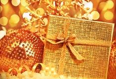 Goldenes Weihnachtsgeschenk mit Flitterdekorationen Stockfotografie