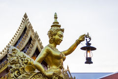 Goldent Ginnaree statue art holding a lamp. Stock Photography
