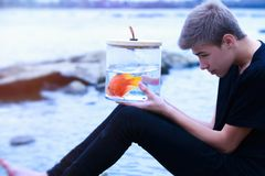 Goldfisch in einer Tasche in den Händen eines Jugendlichen auf dem Strand Stockbild
