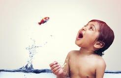 Goldfish που πηδά από το νερό άμεσα στο στόμα παιδιών Στοκ Φωτογραφίες
