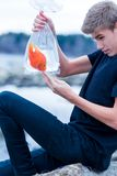 Goldfish in a bag in the hands of a teenager on the beach. Symbols of freedom Stock Images