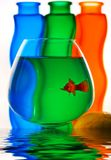 Goldfish in bowl. A goldfish in a bowl in front of colored vases Royalty Free Stock Photography
