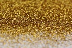 Goldfunkeln-Zusammenfassungshintergrund Stockbilder