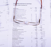 Goldg glasses are on the documents. Royalty Free Stock Images