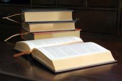 Goldgeprägte Bücher auf hölzernem Schreibtisch Stockbild
