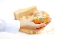 Goldgeschenkbox in der Hand mit dem Band lokalisiert auf weißem backgraund Lizenzfreies Stockbild