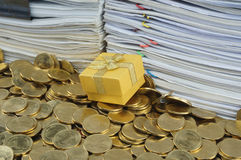 Goldgeschenkbox im Haufen von Münzen stockfotografie