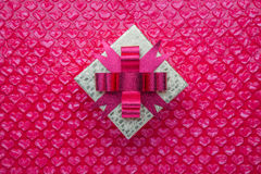 Goldgeschenkbox mit rosa Bogen und rosa Herzen formte Luftpolsterfolie wie Lizenzfreie Stockfotografie