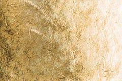 Goldglänzender Folienhintergrund, metallische Beschaffenheit des gelben Glanzes Stockbilder