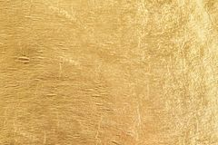 Goldglänzender Folienhintergrund, metallische Beschaffenheit des gelben Glanzes lizenzfreies stockfoto