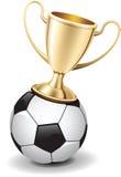 Goldglänzendes Trophäecup oben auf Fußballkugel Lizenzfreie Stockfotografie