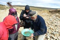 Goldgräber zeigt Touristen den alluvialen Goldsand, der im Bergwerk auf der Insel von Tierra del Fuego gewonnen wird Lizenzfreies Stockbild