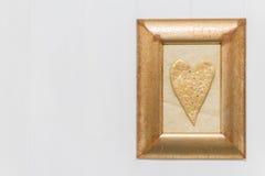Goldherz im Rahmen auf weißem hölzernem Hintergrund Kopieren Sie Platz stockfoto