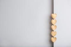 Goldherzaufkleber auf grauem strukturiertem Hintergrund Stockbild