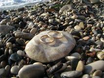 Goldhochzeitsringe auf dem Strand Stockbild