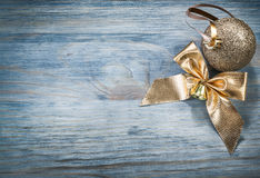 Goldish shiny Christmas ball bow on wooden board copy space holi Stock Photography