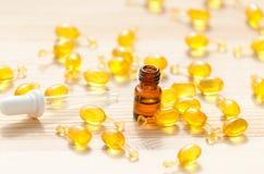 Goldkapseln des natürlichen cosmetik für Gesicht, der 1 ml-Flasche mit ätherischem Öl und der Pipette auf dem hölzernen Lizenzfreies Stockbild