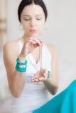 Goldkette in den Händen einer jungen attraktiven orientalischen Frau Verwischender Hintergrund Stockbild