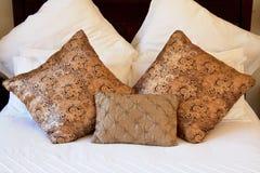 Goldkissen auf weißem Bett Stockfotografie