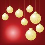 Goldkugel, die am roten Hintergrund am Weihnachtsabend hängt Stockfotografie