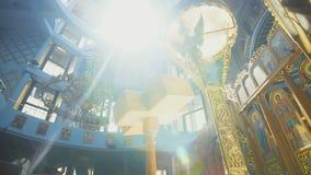 Goldleuchter, der mitten in der schönen Kirche durch das Prisma des Sonnenlichts hängt stock video