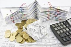Goldmünzeüberlastung von der Geschenkbox und vom Taschenrechner Stockfoto