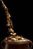 Goldmünzen, die in den Weinlesetopf fallen Lizenzfreie Stockfotografie