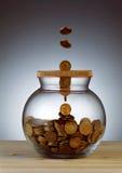 Goldmünzen, die in Glasgefäß fallen Stockbilder