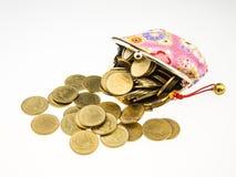 Goldmünzen, die rosa Geldbeutel überlaufen Stockbild