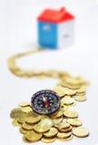 Goldmünzen, Kompass und Haus im weißen Hintergrund Lizenzfreies Stockbild