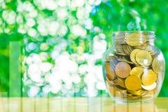 Goldmünzgeld im Glasgefäß auf Tabelle im Garten mit grünem b Stockfotografie