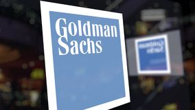 The Goldman Sachs Group, Inc. logo on the glass against blurred business center. Editorial 3D rendering. The Goldman Sachs Group, Inc. logo on the glass against stock video footage