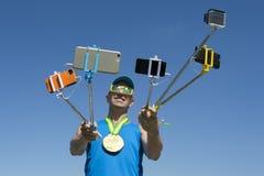 Goldmedaillen-Athlet Taking Selfies mit Selfie-Stöcken stockfoto