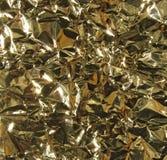 Goldmetallhintergrund - zerknitterte Folie Stockbilder
