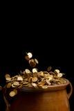 Goldmünzen, die in den Weinlesetopf fallen Stockfotografie