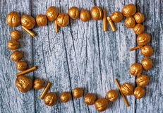 Goldnüsse und Vergoldungsstöcke auf dem Hintergrund von alten Holzverkleidungen, Weihnachtshintergrund Stockbild