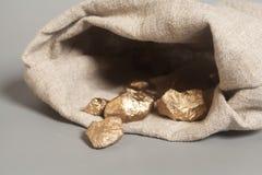 Goldnuggets, die heraus vom Beutel verschüttet werden stockfoto