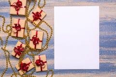 Goldperlen, Geschenke eingewickelt im Kraftpapier mit einem roten Bogen und leeres Papier Stockfotografie