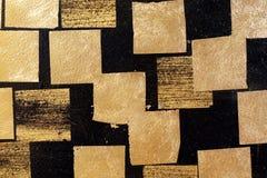 Goldplatte auf Wandschwarzem, Goldblatt, goldene quadratische Folie auf schwarzem Hintergrund, schwarze Fliesenwand mit Goldplatt stockfotografie