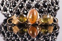 Goldring mit Bernstein und Ohrringen mit grünen Steinen Lizenzfreies Stockfoto