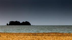 Goldsand mit Schattenbildinsel und -bewölktem Himmel Lizenzfreie Stockbilder