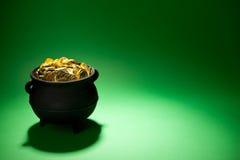 Goldschatz: Voller Topf Münzen auf Grün Stockfotografie