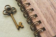 Goldschlüssel und gewundenes Notizbuch auf dem Segeltuchhintergrund Lizenzfreie Stockfotos