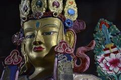 Goldskulptur Buddha, das Gesicht wird mit farbigen Farben, die Krone wird verziert mit Edelsteinen, auf schwarzem Hintergrund ver Stockfotos