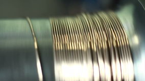 Goldsmith crafting precious metal wire with the help of rolling mill.