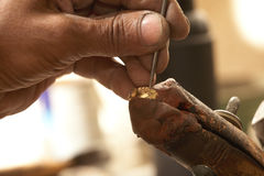 Goldsmith and diamond ring. Goldsmith working on an unfinished 22 carat gold ring with his hard working hands Royalty Free Stock Images