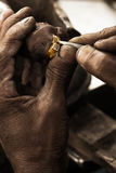 Goldsmith and diamond ring. Goldsmith working on an unfinished 22 carat gold ring with big diamond with his hard working hands. Shallow DOF - focus on the ring Royalty Free Stock Photos