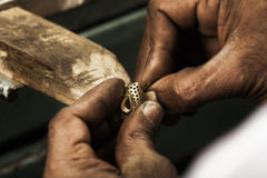 Goldsmith and earring. Goldsmith holding an unfinished 22 carat gold earring in his hard working hands. Shallow DOF - focus on earring. Fine gold dust on hands royalty free stock photography