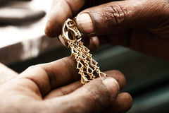 Goldsmith and earring. Goldsmith holding an unfinished 22 carat gold earring in his hard working hands. Fine gold dust on the hands stock images