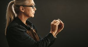 Goldsmith examining the ring. Senior woman jeweler wearing eyeglasses and apron looking at the quality of ring against gray background. Goldsmith examining the stock photo